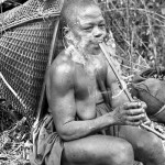 This woman smokes a pipe while taking a break from working on her farm outside Eshobi village, Cameroon. 1966.