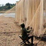 Fisherman mending his nets. Cross River, Mamfe, Cameroon. February 1965.
