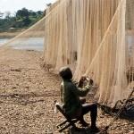 Fisherman mending his nets. Cross River, Mamfe, Cameroon. February 1965.