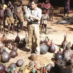 Gerald Durrell holding a black-footed mongoose among yet more calabashes full of small animals. Note the necks of the gourds plugged with local leaves to prevent the escape of the occupants.