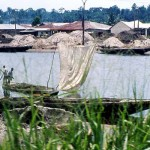 This photo was taken when approaching Lagos on the road from Ibadan, where in places the road ran close to coastal waterways. Sand was dug, often by hand, from the bed of the waterway and then transported by boat to points where it could be collected for use in the building industry. 1977.