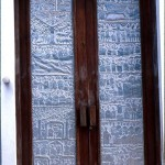 A door of the Catholic Church. The aluminium panels are made by highly skilled local craftsmen and depict a range of themes that reflect the obvious religious nature of the building. 1979.